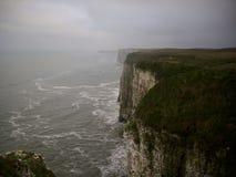 Alta scogliera di gesso con lo spruzzo di mare che forma una foschia Fotografia Stock