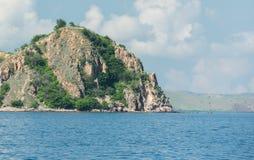 Alta scogliera rocciosa situata sotto il cielo blu con i clo traslucidi Fotografia Stock