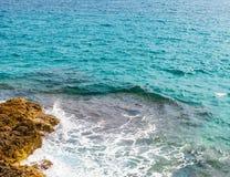 Alta scogliera sopra fondo del mare, mare di estate, molti che spruzzano Immagini Stock