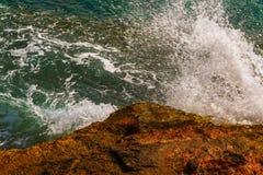 Alta scogliera sopra fondo del mare, mare di estate, molti che spruzzano Immagine Stock