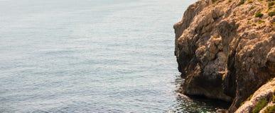 Alta scogliera sopra fondo del mare, mare di estate, molti che spruzzano Fotografie Stock
