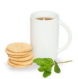Alta tazza bianca di tè con i biscotti e ramoscello della menta Immagine Stock
