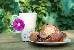 Alta tazza con il fiore sulla tavola Panino fresco su un piatto Immagini Stock
