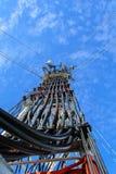 Alta telecomunicazione della costruzione metallica dell'albero sulla torre con la s blu Immagini Stock