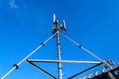 Alta telecomunicazione della costruzione metallica dell'albero sulla torre con la s blu Fotografia Stock
