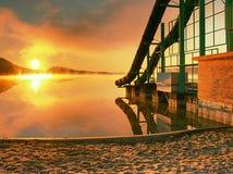 Alta torre d'acciaio con lo scivolamento della pista sulla spiaggia del lago Mattina fredda di autunno con foschia Immagine Stock Libera da Diritti