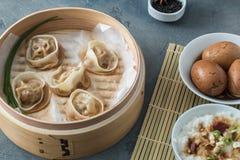Alta vista ad angolo degli gnocchi cucinati dentro il vapore di bambù con il labbro parzialmente fuori Fotografia Stock
