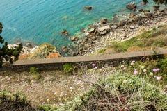 Alta vista della scogliera e delle acque blu della spiaggia Mediterranea sulla costa di Taormina Fotografie Stock Libere da Diritti