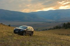 Crossover Nissan X-TRAIL on the hillside in Kurai steppe against the backdrop of the North Chuy ridge at dawn. Altai Krai, Russia - July 15, 2015: Crossover Royalty Free Stock Image