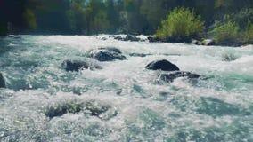 Altai, Kucherla, Rússia - junho, 20, 2018: rio frio da montanha atual Ponto inicial no rio Rochas e árvores Azul claro filme