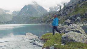 Altai, Kucherla, RUSSIE : Fille contre un lac bleu et des montagnes La fille tourne Mains vers le haut mouvement 4k lent banque de vidéos