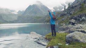 Altai, Kucherla, RUSSIE : Fille contre un lac bleu et des montagnes La fille tourne Mains vers le haut mouvement 4k lent clips vidéos