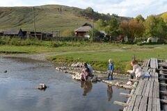 Local residents relax on the mountain river Irovka in the taiga village of Generalka of the Altai Territory