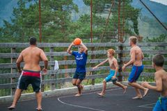 Altai, Russia August 08, 2018. Altai, Russia – August 08, 2018:  young teenagers playing basketball on the basketball court at a children`s camp in the royalty free stock photo