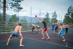 Altai, Russia August 08, 2018. Altai, Russia – August 08, 2018:  young teenagers playing basketball on the basketball court at a children`s camp in the stock photo