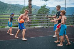 Altai, Russia August 08, 2018. Altai, Russia – August 08, 2018:  young teenagers playing basketball on the basketball court at a children`s camp in the royalty free stock images