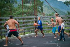 Altai, Russia August 08, 2018. Altai, Russia – August 08, 2018:  young teenagers playing basketball on the basketball court at a children`s camp in the stock images