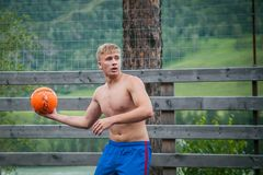 Altai, Russia August 08, 2018. Altai, Russia – August 08, 2018:  young teenagers playing basketball, a young athletic guy is trying to give a pass to his royalty free stock photos