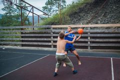 Altai, Russia August 08, 2018. Altai, Russia – August 08, 2018:  young teenagers playing basketball, a young athletic guy is trying to give a pass to his stock photo