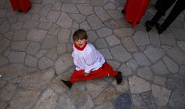 Altar boy during holy week celebrations in the island of mallorca. A young altar boy plays on the ground during Easter holy week processions in the Spanish stock photos