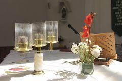 Altar with candlestick, flowers and lectern. The candlestick with three branches, the flowers, red and white and the lectern without book, lighted from the top stock image