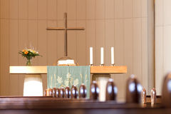 Altar in church. Religious cross, candles and flowers on altar in modern church with wooden pews in foreground Stock Photo