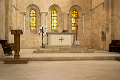 Altar in church. Religious cross, candles on altar and wood lectern in middleage church in Fossanova (italy) with painting windows on background Royalty Free Stock Photography