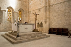 Altar in church. Religious cross, candles on altar in middleage church with painting windows on background Stock Photo