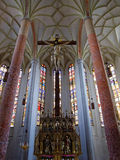 Altar of church St Martin in Lauingen. Jesus Christ statue hanging on the cross above the altar and in front of the stained glass windows of St Martin church in Stock Photography