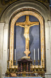 Altar with the crucifixion of Jesus Christ among the candles in the catholic church cathedral basilica of Saint Paul in Rome, Ital Stock Photography