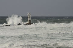 Lighthouse in the wind. Wave in the left, grey sky, white water Stock Photography