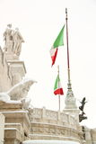 The Altar of Motherland covered by snow. The Alter of Motherland covered by snow, a really rare event in Rome. Italian flags in the wind inflated on the Royalty Free Stock Photos