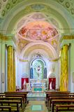 Altar and tabernacle in neoclassical style of an ancient church. Altar and tabernacle of an ancient neoclassical church with columns, cross and representation of Stock Photography