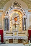 Altar and tabernacle in neoclassical style of an ancient church. Altar and tabernacle of an ancient neoclassical church with columns, cross and representation of Stock Photo