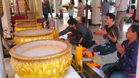 Altar of viharn hall of City Pillar Shrine, Bangkok, Thailand. BANGKOK, THAILAND - APRIL 23, 2019:  The worshipers with burning incense sticks pray in viharn stock video footage