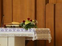 altare di una chiesa cristiana con la bibbia ed il vaso di flowe Immagini Stock