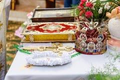 Altare nel tempio cristiano L'incrocio, l'icona, la bibbia e la corona e le fedi nuziali decorati si trovano sull'altare Tradizio fotografie stock libere da diritti