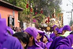 Altarepojke framme av en flöte med Kristus och ett kors på processionen av San Bartolome de Becerra, Antigua, Guatemala Royaltyfria Foton