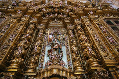 Altarpiece in the New Cathedral of Coimbra. Huge, magnificent gilt wood altarpiece in the national Portuguese artarpiece style, in the New Cathedral or Se Nova royalty free stock photo