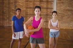 Altas colegialas confiadas que se colocan en la corte con baloncesto Fotografía de archivo