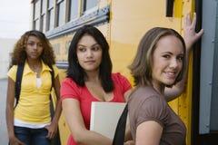 Altas colegialas que consiguen en el autobús escolar Fotografía de archivo