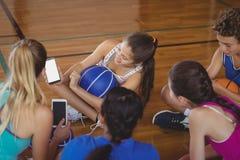 Altas colegialas que miran el teléfono móvil mientras que se relaja en la cancha de básquet Fotografía de archivo