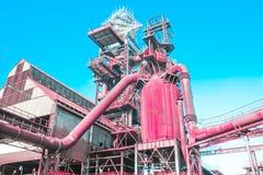 Altas fábricas industriales rosadas coralinas, concepto de un futuro provocativo futurista surrealista y arte de la calle foto de archivo