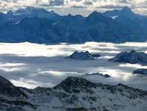 Altas montañas entre las capas de la nube Imágenes de archivo libres de regalías