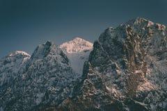 Altas monta?as rocosas hermosas con una monta?a nevosa mientras tanto imagenes de archivo