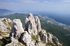 Altas rocas con la cruz contra costa y bosque de mar Fotografía de archivo