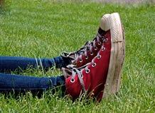 Altas zapatos tenis superiores rojas paralelas en hierba verde Fotos de archivo libres de regalías