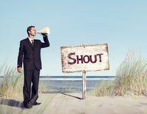 Altavoz de Holding del hombre de negocios con el letrero en la playa foto de archivo libre de regalías