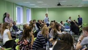 Altavoz famoso con el micrófono en el centro de la audiencia que mira el proceso total del taller Estudiantes adentro almacen de metraje de vídeo