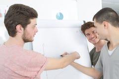 Altavoz masculino en la pantalla delantera del whiteboard que da la presentación Imagenes de archivo
